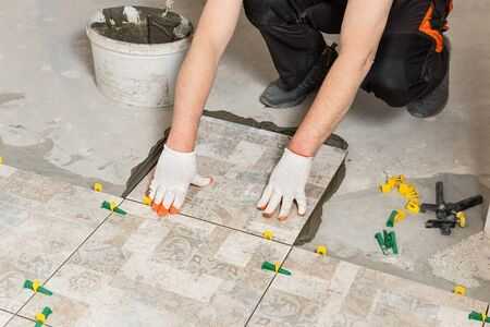 A worker is installing ceramic tiles on the floor. Stockfoto