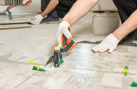 A worker is leveling the ceramic tile with wedges and clips. Stockfoto