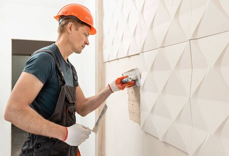 Installation of gypsum 3D panel. The worker is applying adhesive to the wall to attach the gypsum tile.