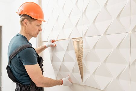 Installation of gypsum 3D panel. The worker is attaching the gypsum tile to the wall.