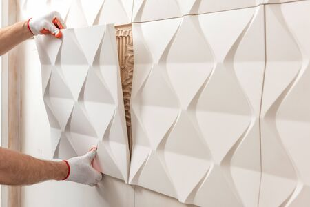 Installation of gypsum 3D panel. A worker is attaching the gypsum tile to the wall.