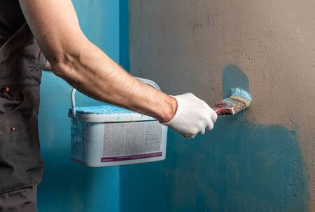 A worker is applying waterproofing paint to the wall in the bathroom.