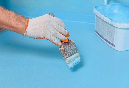 A worker is applying waterproofing paint to the floor in the bathroom. Stockfoto