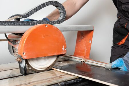 A worker is cutting a ceramic tile on a wet cutter saw  machine. Stockfoto