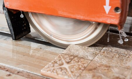 The diamond disk of a wet saw cuts through a ceramic tile.