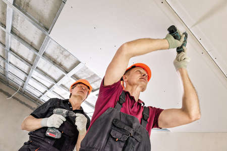 Installation of drywall. Workers are using screws and a screwdriver to attach plasterboard to the ceiling.