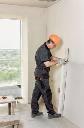 Installation of drywall. The worker is cutting off a piece of drywall. Stockfoto