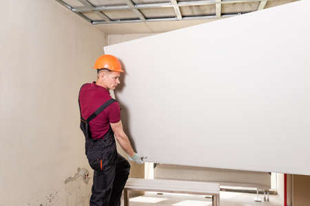 Installation of drywall. The worker is holding drywall for mounting to the ceiling.