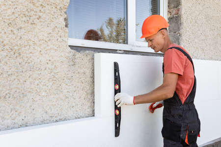 Insulation of the house with polyfoam. The worker is checking with the construction level the accuracy of the installation of polystyrene board on the facade. Archivio Fotografico