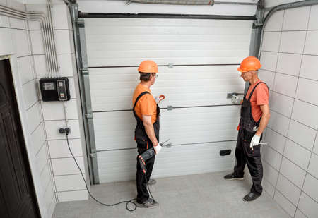 The workers are installing lift gates in the garage. Banque d'images