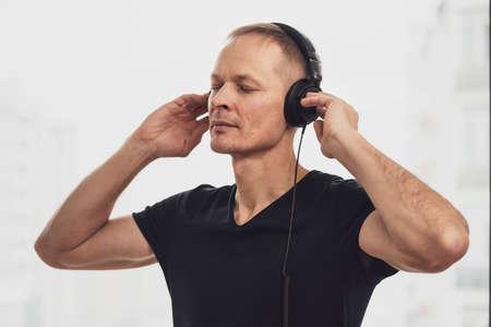 The man in the headphones enjoys listening to music. 免版税图像