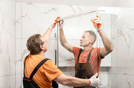 Workers are installing glass door of the shower enclosure.