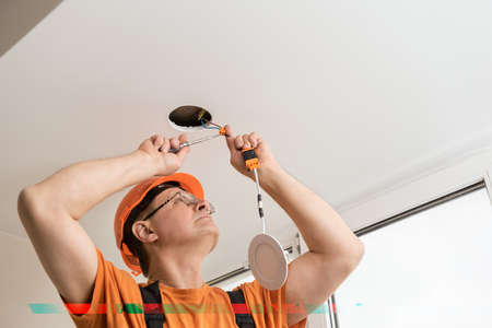 The electrician is installing an LED spotlight in the ceiling. Фото со стока