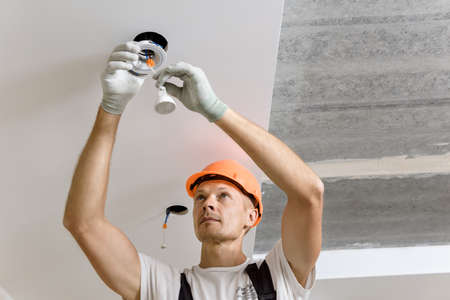 The electrician is installing LED spotlights on the ceiling.