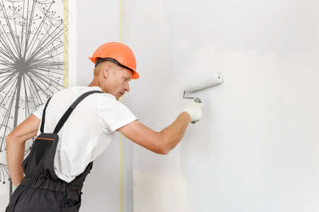 The painter is painting a wall in a room with a roller.