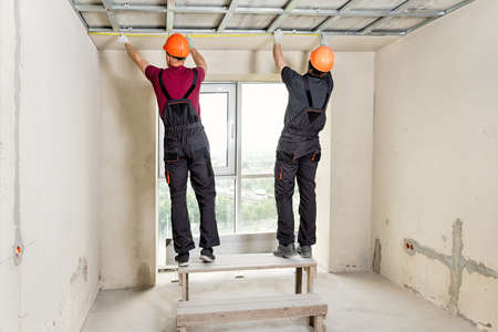 Installation of drywall. Workers are measuring the ceiling. Фото со стока
