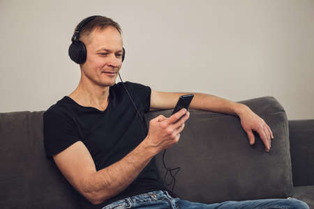 The man in headphones and with a smartphone sits on the couch. Фото со стока