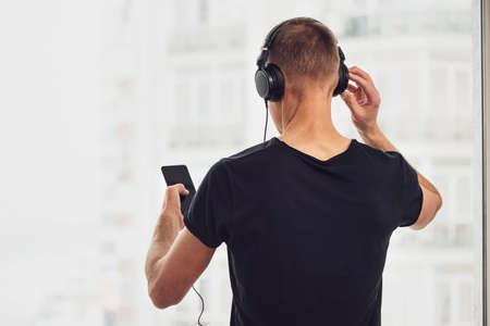 The man in headphones and with a smartphone. Back view. Фото со стока