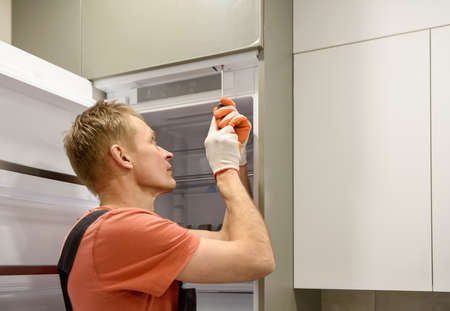 The worker is fixing the built-in refrigerator in the kitchen furniture.