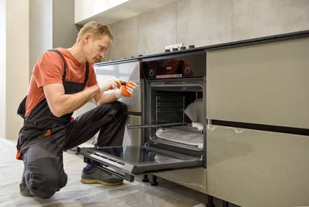 The worker is installing an electric oven in the kitchen furniture. Фото со стока