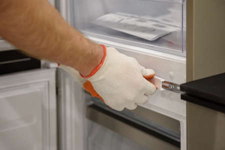 A worker is fixing the built-in refrigerator in the kitchen furniture.