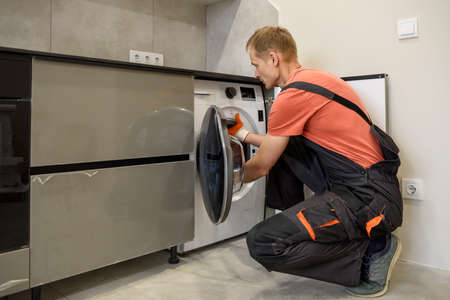 The worker is installing a washing machine in the kitchen furniture. Фото со стока