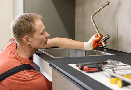 The plumber is installing a faucet on the kitchen sink.