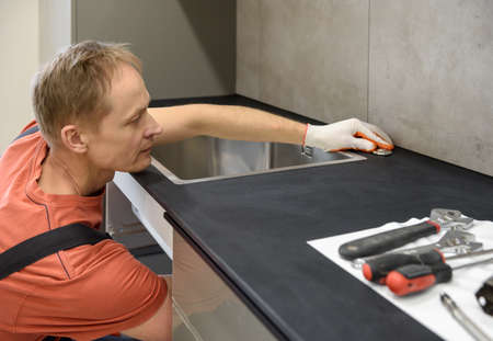 The plumber is setting the start button for the waste shredder on the kitchen sink.