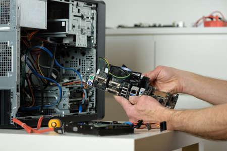 A technician is holding the motherboard in a desktop case. Фото со стока