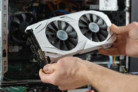 Human hands are inserting a video card into a computer.