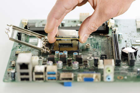 The human hand is installing the processor on the motherboard.