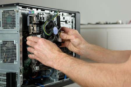 A technician is installing the motherboard in the desktop case.