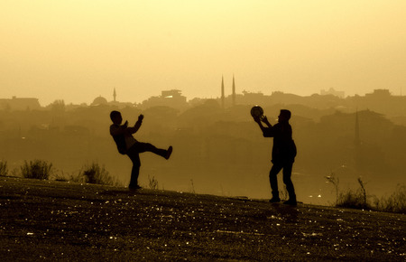 foggy hill: Foggy day, hill kids playing ball, rear view looks istanbul houses and mosques.