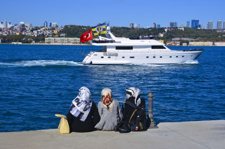 three women: Istanbul, Turkey - October 20, 2013: Sea of Marmara, the Bosphorus. Middle East three women sitting on the beach, looking at the sea resting.