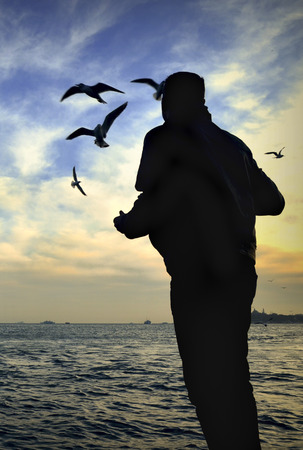 istanbul beach: Sunset seagulls and people silhouette. Stock Photo