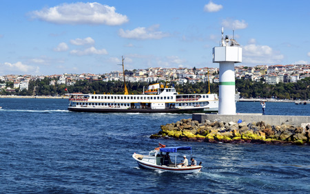 Istanbul, Turkey - September 9, 2012:  Ferries in Istanbul.Istanbul, Haydarpasa Coastal Breakwater Lighthouse on. Boats have traversed the waters of the Bosphorus for millennia and until the opening of the first Bosphorus bridge in 1973, were the only mod Editorial