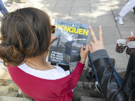guy fawkes mask: Istanbul, Turkey - June 5, 2013: The magazine readers Examines news about protests in Gezi Park. A wave of Demonstrations and civil unrest in Turkey beg on 28 May 2013. Initially to contest the urban development plan for Istanbuls Taksim Gezi Park. The p