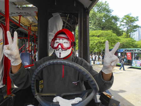 guy fawkes mask: Istanbul, Turkey - June 9, 2013: in protests in Taksim suffered damage municipality buses. A wave of demonstrations and civil unrest in Turkey began on 28 May 2013, initially to contest the urban development plan for Istanbuls Taksim Gezi Park. The prote