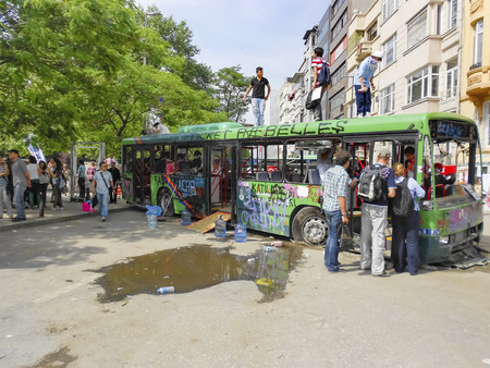 guy fawkes mask: Istanbul, Turkey - June 9, 2013:  Gezi Park protests. Damaged public bus being used as barricade.  A wave of demonstrations and civil unrest in Turkey began on 28 May 2013, initially to contest the urban development plan for Istanbuls Taksim Gezi Park. T
