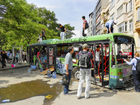 guy fawkes: Istanbul, Turkey - June 9, 2013:  Gezi Park protests. Damaged public bus being used as barricade.  A wave of demonstrations and civil unrest in Turkey began on 28 May 2013, initially to contest the urban development plan for Istanbuls Taksim Gezi Park. T