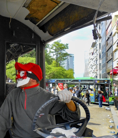 protester: Istanbul, Turkey - June 9, 2013: Protester wearing a Guy Fawkes mask,  in protests in Taksim suffered damage municipality buses. A wave of demonstrations and civil unrest in Turkey began on 28 May 2013, initially to contest the urban development plan for  Editorial