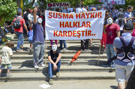 demonstrators: Istanbul, Turkey - June 9, 2013: Travel Park protests.guy Fawkes masked demonstrators with placards seen in Travel park.th a sit-in at Taksim Gezi Park was restored after police withdrew from Taksim Square on 1 June, and developed into an Occupy- like cam