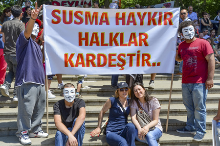 fawkes: Istanbul, Turkey - June 9, 2013: Travel Park protests.guy Fawkes masked demonstrators with placards seen in Travel park.th a sit-in at Taksim Gezi Park was restored after police withdrew from Taksim Square on 1 June, and developed into an Occupy- like cam