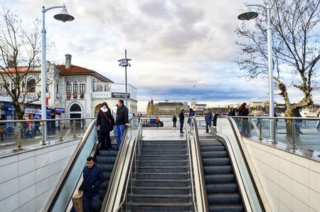 koy: Istanbul, Turkey - January 19, 2013: Old Kadikoy Pier. New Kadikoy-Kartal subway exit Kadikoy. On a cold winter day moving subway and ferry stop people.