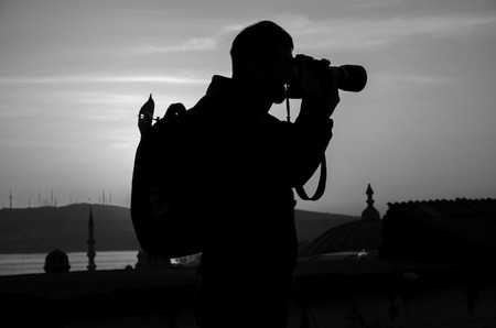 documenting: Sunrise silhouette of photographers shooting, at dawn