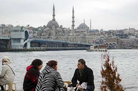 istanbul beach: Istanbul, Turkey - February 26, 2013: Istanbul Golden Horn boats at sea. People who eat fish on the beach bread. Galata bridge and Eminonu looks new mosque in the background.