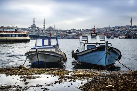 eminonu: Istanbul Golden Horn boats at sea. Galata bridge and Eminonu looks new mosque in the background.