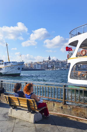 Istanbul, Turkey - July 26, 2016: Istanbul Eminonu ferry pier, dock people. This is a great place to see the colors of Istanbul at . Interesting to see the fishermen on the bridge with the Galata tower in the background. There are lots of restaurants on t Editorial