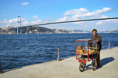 Istanbul, Turkey - March 10, 2013: Turkish vendor sells bagels, a type of Turkish bread, in the coast of Istanbul on the Bosphorus. In the background Istanbul July 15 martyrs bridge. and European Side (Turkish: Avrupa Yakasi) is the western half of Ista Editorial