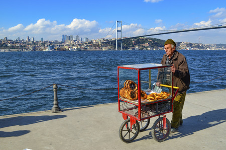 turkish bread: Istanbul, Turkey - March 10, 2013: Turkish vendor sells bagels, a type of Turkish bread, in the coast of Istanbul on the Bosphorus. In the background Istanbul July 15 martyrs bridge. and European Side (Turkish: Avrupa Yakasi) is the western half of Ista Editorial